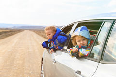 Little girl and boy travel by car on the road Stock Images
