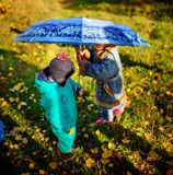 Little girl and boy with umbrella playing in the rain. Kids play outdoor by rainy weather in fall. Autumn fun for children. Toddle Stock Image