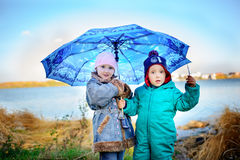 Little girl and boy with umbrella playing in the rain. Kids play outdoor by rainy weather in fall. Autumn fun for children. Toddle Stock Photo