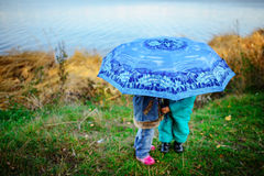 Little girl and boy with umbrella playing in the rain. Kids play outdoor by rainy weather in fall. Autumn fun for children. Toddle Royalty Free Stock Photography
