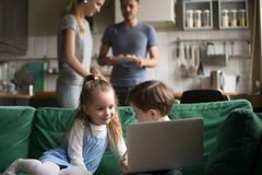 Little girl and boy using laptop while parents cooking stock photo