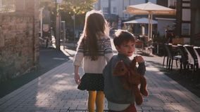 Little girl and boy walk together holding hands. Slow motion. Back view. Two kids wander around old town on a sunny day.