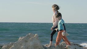 Little girl and boy walks along beach near sea, homeless children, against background ocean at sunset. kid goes together with his stock footage