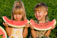 Little girl and boy with watermelon. Little blond girl and boy with a piece of watermelon in hands Royalty Free Stock Photography