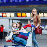 Little girl and boy and young mother with suitcases on airport Royalty Free Stock Photos