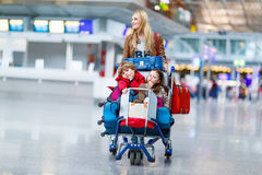 Little girl and boy and young mother with suitcases on airport. Two adorable little siblings, kid boy and girl sitting on suitcases on international airport Stock Image