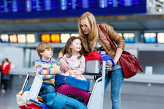 Little girl and boy and young mother with suitcases on airport. Two adorable little siblings, kid boy and girl sitting on suitcases on international airport Royalty Free Stock Photography