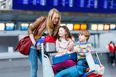Little girl and boy and young mother with suitcases on airport. Two adorable little siblings, kid boy and girl sitting on suitcases on international airport Royalty Free Stock Photos