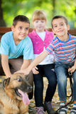 Little girl and boys in the park with a German Shepherd Royalty Free Stock Images