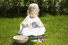 Little girl with bracelet on grass. Cute little girl in white dress playing with bracelet on the grass in summertime Stock Image