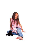 Little Girl With Braids. Little African American girl with finger braids sitting on the floor with a stuffed animals at her feet Stock Photos