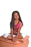 Little Girl With Braids. Little African American girl with finger braids sitting foot stool with her legs crossed Stock Photography