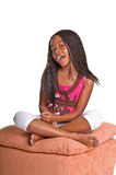 Little Girl With Braids. Little African American girl with finger braids sitting foot stool with her legs crossed Stock Photos