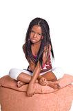 Little Girl With Braids. Little African American girl with finger braids sitting foot stool with her legs crossed looking sad Stock Image