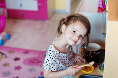 Little girl with braids drawing playing with toy kitchen Stock Photo