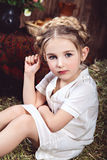 Little girl with braids on hay Stock Photo