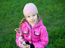 Little girl with branch of flowers Stock Image