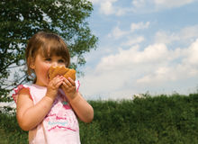 Little girl with a bread Stock Image