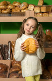 Little girl with bread in hand. bread's  shelves  background . S Stock Photos