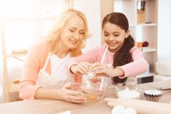 Little girl breaks egg into bowl, sitting with her grandmother in kitchen. stock images