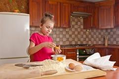 Little girl breaks the egg Stock Images