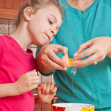 Little girl breaks the egg with mom Royalty Free Stock Image
