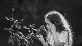 Little girl breathe scent of rose flowers. Black and white portr Stock Images