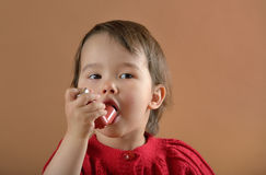 Little girl breathing asthmatic medicine inhaler. Little girl breathing asthmatic medicine health-care inhaler royalty free stock photography