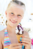 Little girl in the bright bathing suit eating a delicious ice cr Royalty Free Stock Image