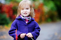 Little girl in bright blue coat at autumn Stock Photos