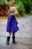 Little girl in bright blue coat at autumn Royalty Free Stock Photography