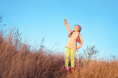 Little girl in bright clothes with scooter shows a finger to the sky Royalty Free Stock Image