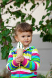 Little girl in a bright colored clothes eats ice-cream. Stock Photo