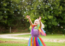 A little girl in a bright costume chasing bubbles Stock Photo