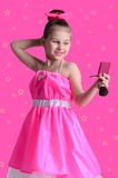 Little girl in a bright dress looks in the mirror and doing make Royalty Free Stock Photography