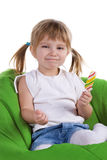 Little girl with a bright lollipop on armchair Stock Photography