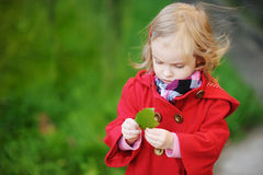Little girl in bright red coat at autumn Royalty Free Stock Images