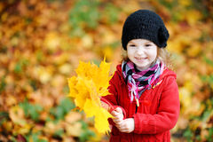 Little girl in bright red coat at autumn Royalty Free Stock Photography
