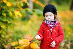 Little girl in bright red coat at autumn Stock Image