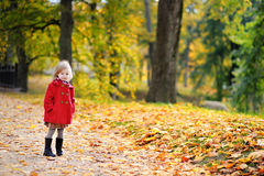 Little girl in bright red coat at autumn Royalty Free Stock Photo