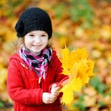 Little girl in bright red coat at autumn Royalty Free Stock Image