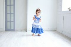 Little girl in bright room. Funny and cute brunette little smiling girl playing and dancing in bright room Royalty Free Stock Photos