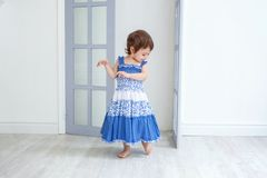 Little girl in bright room. Funny and cute brunette little smiling girl playing and dancing in bright room Stock Photos