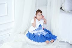Little girl in bright room. Funny and cute brunette little smiling girl sits on fluffy carpet in bright room Stock Images