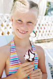 Little girl in the bright swimsuit eating a delicious ice cr Stock Image