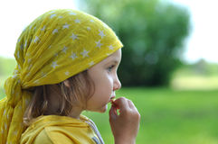 A little girl in a bright yellow bandanna eating a biscuit Royalty Free Stock Photography