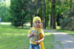 A little girl in a bright yellow bandanna eating a biscuit Royalty Free Stock Images