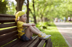 A little girl in a bright yellow bandanna and yellow snaekers sitting on a bench Royalty Free Stock Photos
