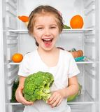 Little girl  against a refrigerator Royalty Free Stock Photography