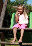 Little girl with broken hand on slide Stock Photo